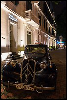 Vintage car in front of Metropole hotel at night. Hanoi, Vietnam (color)