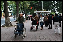 Elderly women pushing their wheelchairs while walking for exercise. Hanoi, Vietnam (color)