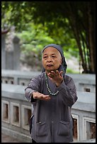 Elderly woman doing Tai Chi moves. Hanoi, Vietnam ( color)