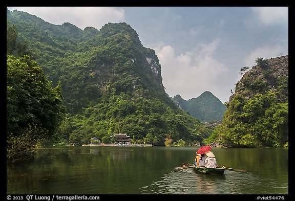 Boat journeying below tall lush cliffs, Trang An. Ninh Binh,  Vietnam (color)