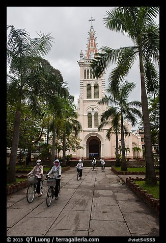Students biking past Cho Quan Church, district 11. Ho Chi Minh City, Vietnam (color)