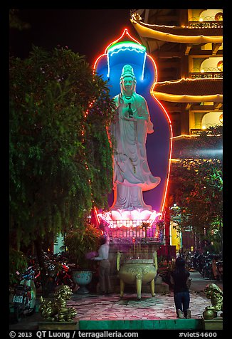 Praying outside Quoc Tu Pagoda at night, district 10. Ho Chi Minh City, Vietnam (color)