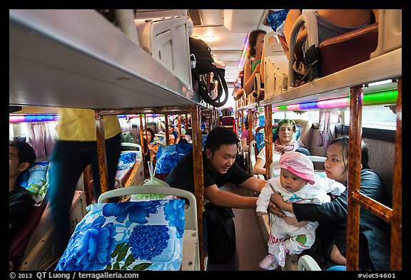 Couple passing baby on sleeper bus. Vietnam (color)