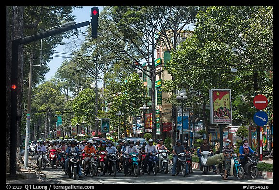 Motorcyclists on tree-lined street, district 5. Ho Chi Minh City, Vietnam (color)