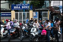 School entrance with parents waiting on motorbikes. Ho Chi Minh City, Vietnam
