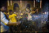 Revellers celebrating with spray in front of Notre Dame Cathedral on Christmas Eve. Ho Chi Minh City, Vietnam (color)