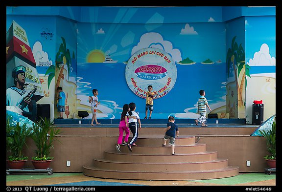 Children on stage next to militaristic mural, Dam Sen Water Park, district 11. Ho Chi Minh City, Vietnam (color)