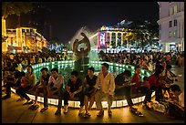 People sitting on fountain at night, New Year eve. Ho Chi Minh City, Vietnam (color)