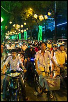 Street packed with motorbikes and bicycle riders at night. Ho Chi Minh City, Vietnam (color)