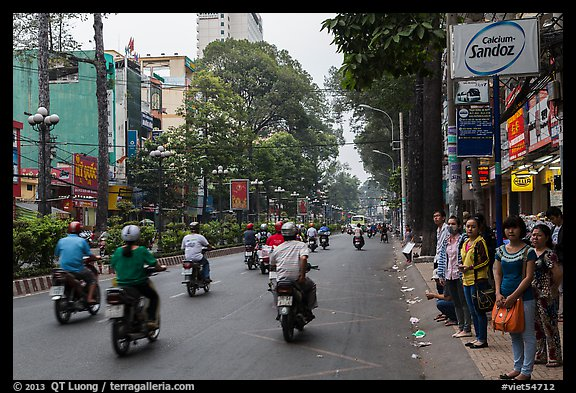 Motorbike traffic and pedestrians waiting for bus. Ho Chi Minh City, Vietnam (color)