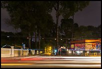 Traffic light trails and tall trees next to Van Hoa Park. Ho Chi Minh City, Vietnam