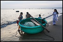 Family around their coracle boat. Mui Ne, Vietnam (color)