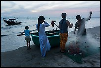 Fishermen folding net out of coracle boat as children watch. Mui Ne, Vietnam (color)