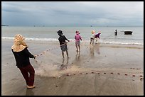 Fishermen lining up to pull net onto beach. Mui Ne, Vietnam (color)