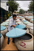 Man lifting covers of jars with fermented fish sauce. Mui Ne, Vietnam (color)