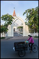 Woman bicycling in front of church. Tra Vinh, Vietnam (color)