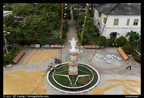 View of drying rice and statue from church tower. Tra Vinh, Vietnam (color)