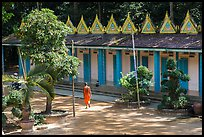 Monk walking past huts, Hang Pagoda. Tra Vinh, Vietnam ( color)