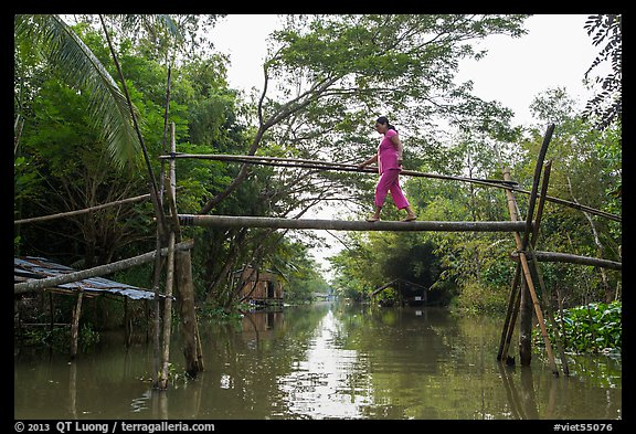 Woman traversing monkey bridge. Can Tho, Vietnam (color)