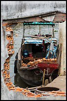 Boat loaded with bricks seen from brick wall opening. Can Tho, Vietnam (color)