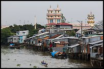 Riverside houses on stilts and Cao Dai temple. Mekong Delta, Vietnam ( color)
