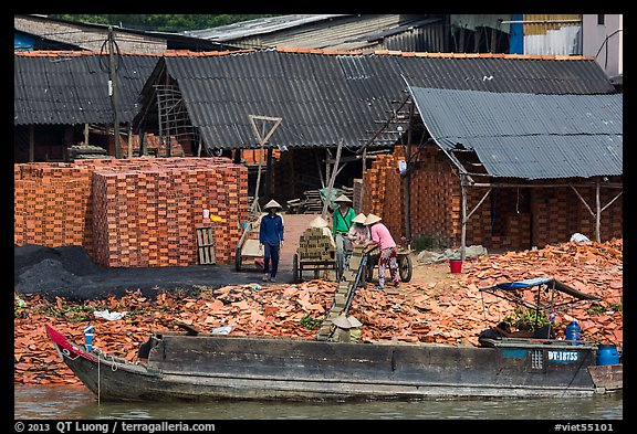Workers loading bricks on boat. Sa Dec, Vietnam (color)