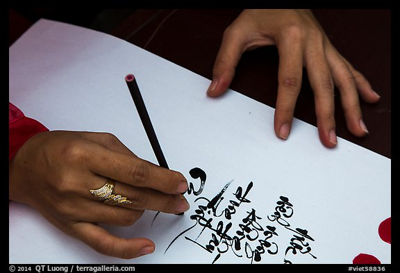 Feminine hand draws Lunar New Year greetings in fancy writing. Ho Chi Minh City, Vietnam (color)