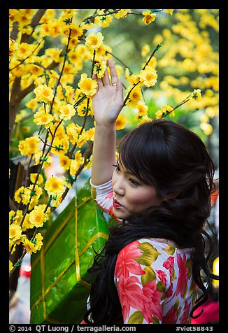 Woman next to Tet (Lunar New Year) decorations. Ho Chi Minh City, Vietnam (color)