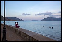 Young women sitting on seawall, evening, Con Son. Con Dao Islands, Vietnam ( color)
