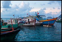 Fishing boats and man standing on raft, early morning, Con Son harbor. Con Dao Islands, Vietnam ( color)