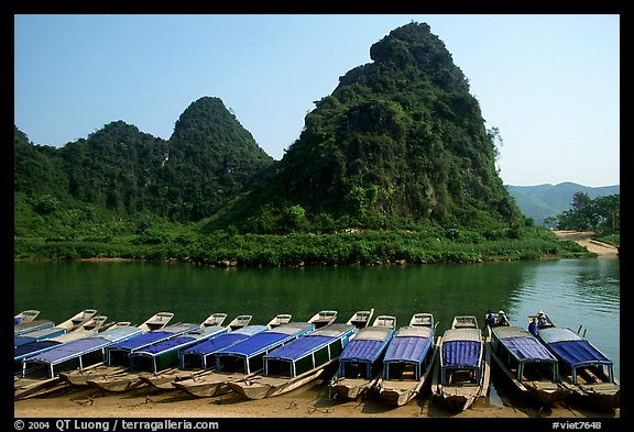 Tour boats and forest-covered limestone rocks, Son Trach. Vietnam