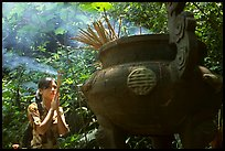 Visitor praying at an urn with incense near the entrance of Phong Nha Cave. Vietnam (color)