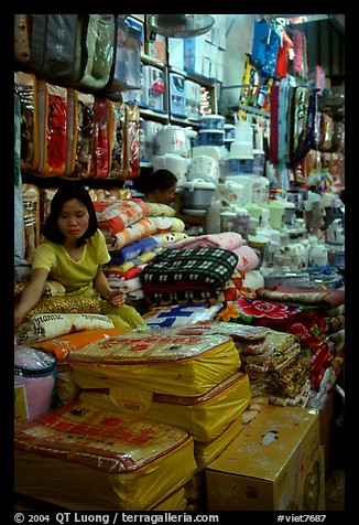 Vendor sitting amongst Abondance of cheap goods imported from nearby China at the Dong Kinh Market. Lang Son, Northest Vietnam (color)