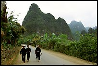 Villagers in traditional garb walking down the road with limestone peaks in the background, Ma Phuoc Pass area. Northeast Vietnam