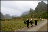 Villagers walking down the road with limestone peaks in the background, Ma Phuoc Pass area. Northeast Vietnam