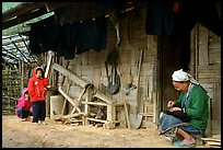 Elderly woman sewing  on her doorstep as kids look up. Northeast Vietnam