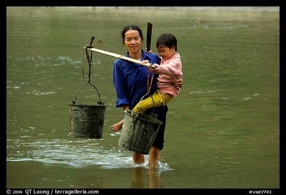 Tay Woman carrying child and water buckets across river. Northeast Vietnam