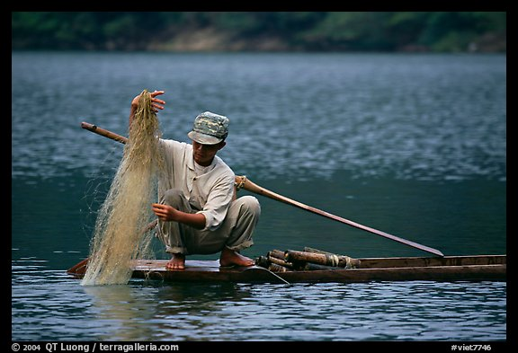 Fisherman retrieves net from a dugout boat. Northeast Vietnam