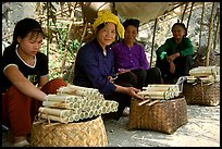 Women selling sweet rice cooked in bamboo tubes. Vietnam (color)