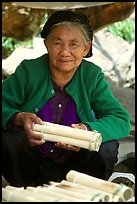 Woman selling sweet rice cooked in bamboo tubes. Vietnam ( color)