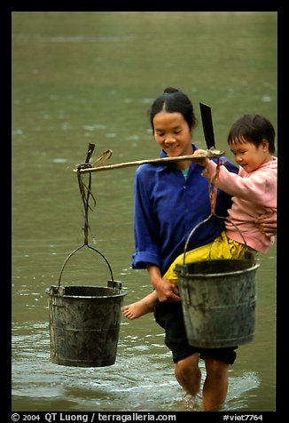 Woman of the Tay minority carrying crossing the river with child, Ba Be Lake. Vietnam (color)