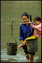 Woman of the Tay minority carrying crossing the river with child, Ba Be Lake. Vietnam