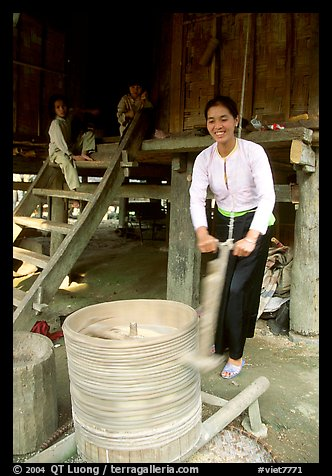 Woman of the Thai ethnicity milling grain, near Mai Chau. Northwest Vietnam