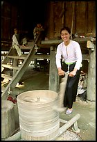 Woman of the Thai ethnicity milling grain, near Mai Chau. Northwest Vietnam (color)
