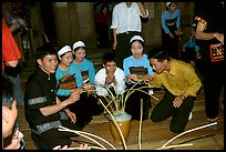 Thai women and guests drinking rau can alcohol with long straws, Ban Lac, Mai Chau. Northwest Vietnam