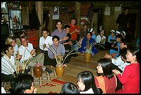 Guests in a thai house gather around jars of rau can alcohol, Ban Lac, Mai Chau. Northwest Vietnam