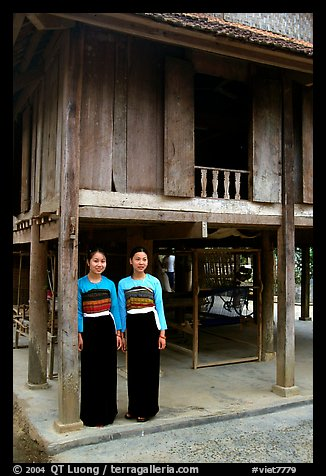 Two thai women standing in front of their stilt house, Ban Lac village. Northwest Vietnam (color)
