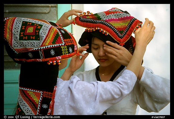 A thai woman helps her friend with her elaborate headdress, Son La. Northwest Vietnam (color)