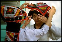 A thai woman helps her friend with her elaborate headdress, Son La. Northwest Vietnam