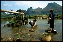 Thai women washing laundry and collecting water plants near an irrigation wheel, near Son La. Northwest Vietnam ( color)